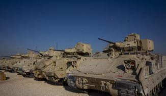 In this Nov. 11, 2019, file photo, Bradley fighting vehicles are parked at a U.S. military base at an undisclosed location in Northeastern Syria, Monday, Nov. 11, 2019. Reuters is reporting that 500 U.S. troops, 25 Abrams tanks and 30 Bradley armored vehicles are set to replace existing forces that arrived in Lithuania earlier in September 2020. (AP Photo/Darko Bandic, File)