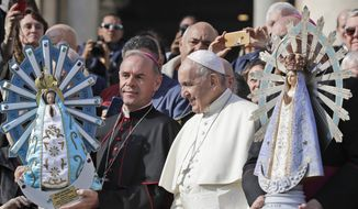 In this Oct. 30, 2019, file photo, Pope Francis poses for photographs with British Bishop Paul Mason, left, as they hold statues of Our Lady of Lujan, the original held at right, and its replica, left, at the end of his weekly general audience in St. Peter's Square, at the Vatican. Pope Francis is giving his blessing to a new Vatican think tank that is seeking to prevent the Mafia and organized crime groups from exploiting the image of the Virgin Mary for their own illicit ends. (AP Photo/Andrew Medichini)