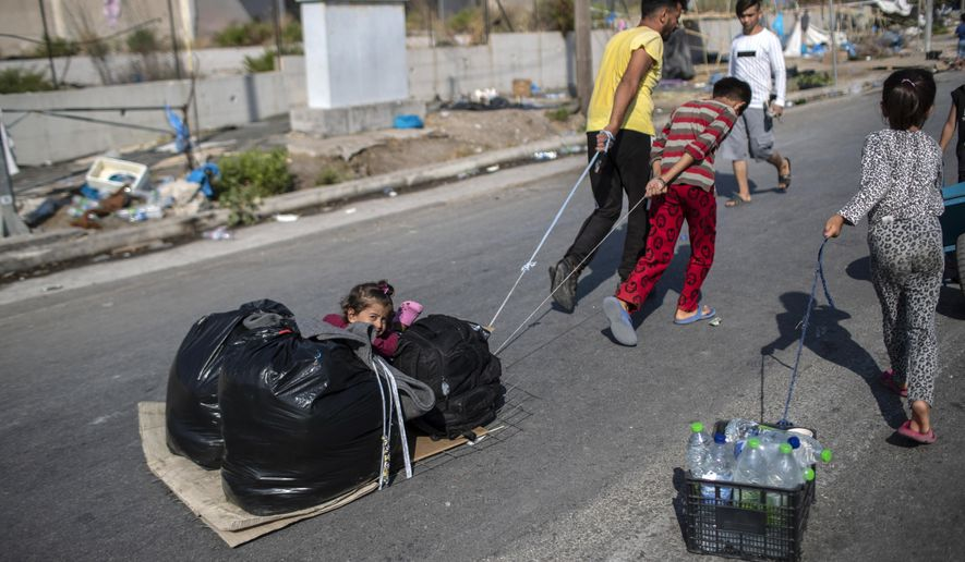 A child sits between plastic bags as migrants pull their belongings in Kara Tepe, near Mytilene the capital of the northeastern island of Lesbos, Greece, Thursday, Sept. 17, 2020. Greek police are moving hundreds of migrants to an army-built camp on the island of Lesbos Thursday after a fire destroyed an overcrowded facility, leaving them homeless for days. (AP Photo/Petros Giannakouris)