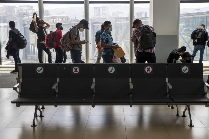 Passengers wait to board a humanitarian flight to Canada at the La Aurora international airport in Guatemala City, Thursday, Sept. 17, 2020. Authorities are preparing for the reopening of the airport on Friday as part of the gradual reopening of the country's borders by allowing national flights and some duly authorized international flights. (AP Photo/Moises Castillo)