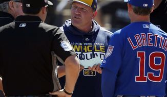 """FILE - In this March 10, 2019, file photo, Milwaukee Brewers bench coach Pat Murphy, center, talks with Chicago Cubs bench coach Mark Loretta (19) and the umpires before a spring training baseball game in Phoenix. Murphy has rejoined the team six weeks after suffering a heart attack at Miller Park. Murphy said he was feeling """"pretty good"""" while talking to reporters before the Brewers' Friday, Sept. 18, 2020, game with the Kansas City Royals. (AP Photo/Sue Ogrocki, File)"""