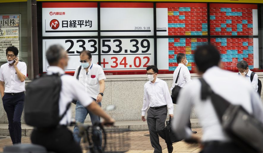 Men walk by screens showing Japan's Nikkei 225 index at a securities firm in Tokyo on Friday, Sept. 18, 2020. Asian shares were slightly higher Friday despite some investor attention shifting again to the uncertainties in global economies amid the coronavirus pandemic, as reflected in the overnight fall on Wall Street.(AP Photo/Hiro Komae)