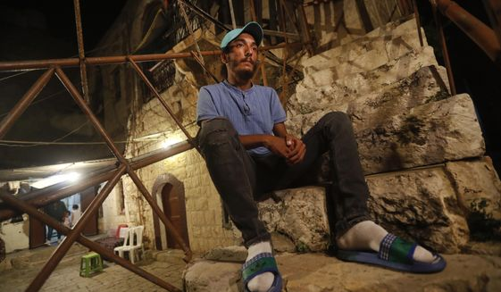 Lebanese Mohammed Sufian, 21, sits outside his house, in Tripoli, north Lebanon Thursday, Sept. 17, 2020, days after he was rescued at sea by a U.N. naval force after trying to migrate with his family on a boat to Cyprus. He ended up losing his two-year-old son as a result of severe heat with no food or water on board. Mohammed is among dozens of people who have tried in recent weeks to flee Lebanon to Europe amid a devastating and unprecedented economic and financial crisis. (AP Photo/Hussein Malla)