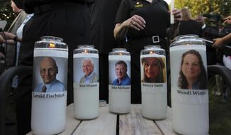 FILE - In this June 29, 2018, file photo, of five employees of the Capital Gazette newspaper adorn candles during a vigil across the street from where they were slain in the newsroom in Annapolis, Md.  A judge has ruled Friday, Sept. 18, 2020,  a psychiatrist retained by prosecutors in the case of a man who killed five people at a Maryland newspaper can testify about whether he believes the gunman was criminally responsible in the sanity phase of his trial.   (AP Photo/Jose Luis Magana, File)