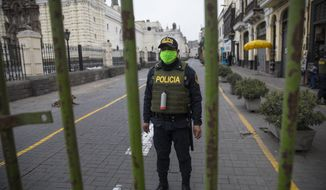 A police officer stands guard one block away from the Constitutional Court building in Lima, Peru, Thursday, Sept. 17, 2020. The court rejected a request by President Martin Vizcarra Thursday to halt impeachment proceedings being pushed by opposition lawmakers who contend he tried to cover up ties with a controversial ally. (AP Photo/Rodrigo Abd)