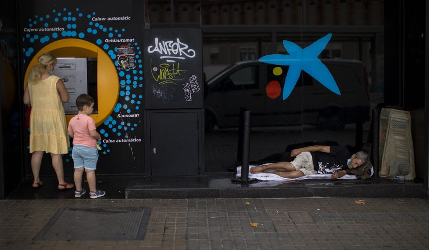FILE, In this Friday July 17, 2020 file photo, a child looks at a man sleeping outside a CaixaBank brach office in Barcelona, Spain.  Two of Spain's biggest banks are poised to merge and create the country's largest bank in terms of domestic operations, with assets of more than 600 billion euros (dollars 708 billion). The deal brings the prospect of more job losses amid difficult times for the financial sector. A tie-up between CaixaBank, the largest bank in the domestic market, and Bankia, Spain's biggest mortgage lender, could herald other moves toward consolidation in the financial sector. (AP Photo/Emilio Morenatti)