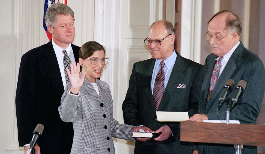 FILE - In this Aug. 10, 1993, file photo, Supreme Court Justice Ruth Bader Ginsburg takes the court oath from Chief Justice William Rehnquist, right, during a ceremony in the East Room of the White House in Washington. Ginsburg's husband Martin holds the Bible and President Bill Clinton watches at left. The Supreme Court says Ginsburg has died of metastatic pancreatic cancer at age 87. (AP Photo/Marcy Nighswander, File)