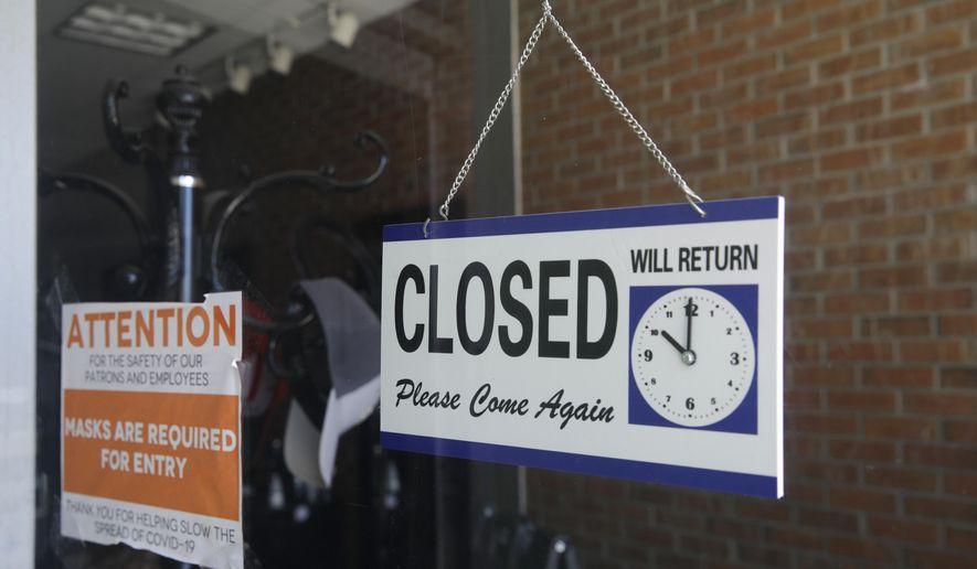In this July 18, 2020, file photo a closed sign hangs in the window of a barbershop in Burbank, Calif. (AP Photo/Marcio Jose Sanchez, File)