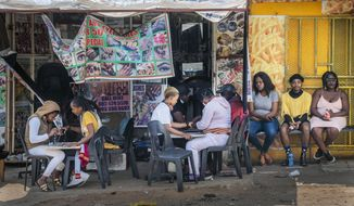 FILE - In this Sept. 16, 2020 file photo, customers have their nails done near the Baragwanath taxi rank in Soweto, South Africa. The country's success in bringing its first wave of COVID-19 under control has allowed it to almost fully reopen the economy, while monitoring for signs of a second surge, says the government's chief medical advisor. (AP Photo/Jerome Delay, File)