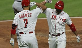 Cincinnati Reds' Eugenio Suarez, left, congratulates Joey Votto, who hit a solo home run during the third inning of the team's baseball game against the Chicago White Sox in Cincinnati, Friday, Sept. 18, 2020. (AP Photo/Aaron Doster)