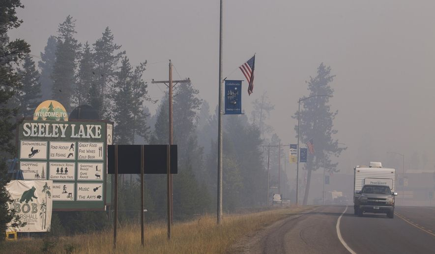 FILE - In this Aug. 10, 2017, file photo provided by the U.S. Forest Service, a pickup truck pulls a camper through the wildfire smoke in Seeley Lake in Missoula County, Mont. The small town was blanketed with hazardous smoke due to wildfires for seven weeks in 2017. A study showed residents' lung capacity declined in the first two years after the fires. The study team hasn't been able to return to Seeley Lake to check on the residents this year because of the coronavirus pandemic. (Kari Greer, U.S. Forest Service via AP, File)