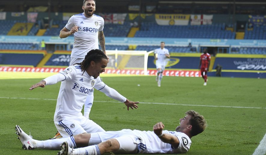 Leeds United's Helder Costa, left, celebrates with teammates after scoring his side's fourth goal during the English Premier League soccer match between Leeds United and Fulham at Elland Road Stadium, in Leeds, England, Saturday, Sept. 19, 2020. (Oli Scarff/Pool via AP)