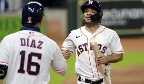 Houston Astros' Aledmys Diaz, left, congratulates Jose Altuve, right, after he scores the go-ahead run on the single by Kyle Tucker during the sixth inning of a baseball game against the Arizona Diamondbacks Saturday, Sept. 19, 2020, in Houston. (AP Photo/Michael Wyke)