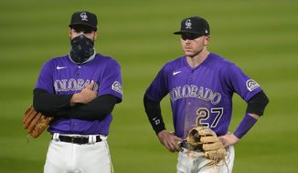 Colorado Rockies third baseman Nolan Arenado, left, and shortstop Trtevor Story watch as relief pitcher Tyler Kinley warms up after replacing Wade Davis during the seventh inning of the team's baseball game against the Los Angeles Dodgers on Friday, Sept. 18, 2020, in Denver. The Dodgers won 15-6. (AP Photo/David Zalubowski)