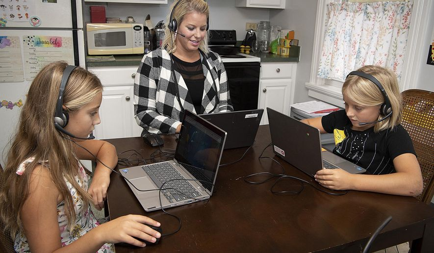 In this file photo from Sept. 17, 2020, a mother and her two daughters are at their laptops doing school work around their Frederick, Md., kitchen table. (Bill Green/The Frederick News-Post via AP)