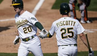 Oakland Athletics' Mark Canha (20) is congratulated by Stephen Piscotty after scoring against the San Francisco Giants in the fourth inning of a baseball game in Oakland, Calif., Saturday, Sept. 19, 2020. (AP Photo/Jeff Chiu)