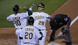Oakland Athletics' Matt Olson (28) is greeted by Marcus Semien (10) and Mark Canha (20) after hitting a three-run home run off San Francisco Giants starting pitcher Logan Webb during the third inning of a baseball game Friday, Sept. 18, 2020, in Oakland, Calif. (AP Photo/Eric Risberg)