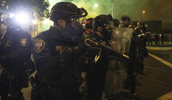 Tear gas fills the air as police take control of the streets during protests, Friday, Sept. 18, 2020, in Portland, Ore. (AP Photo/Paula Bronstein)  ** FILE **