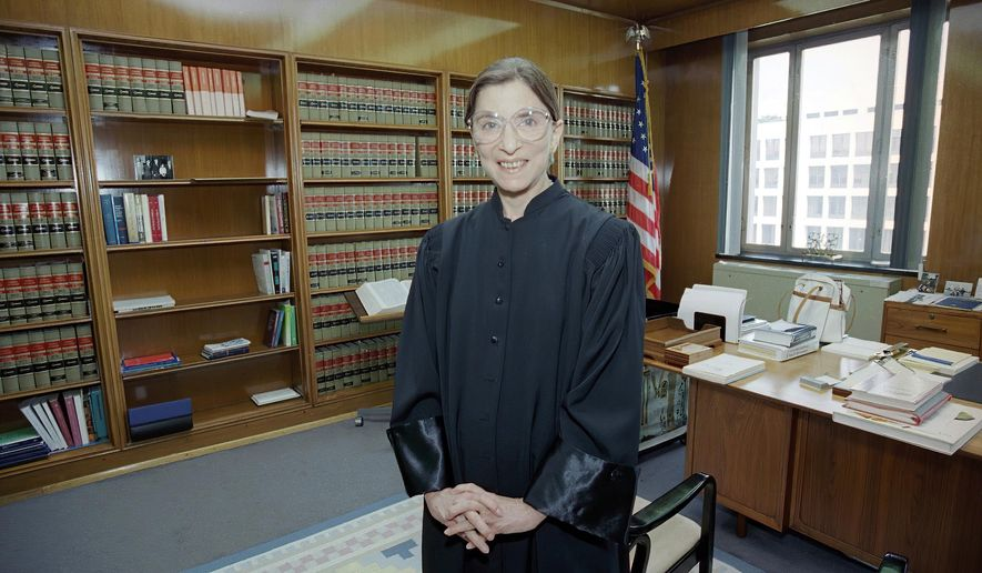 In this Aug. 3, 1993, file photo, then-Judge Ruth Bader Ginsburg poses in her robe in her office at U.S. District Court in Washington. Earlier, the Senate voted 96-3 to confirm Bader as the 107th justice and the second woman to serve on the Supreme Court. Ruth Bader Ginsburg died at her home in Washington, on Sept. 18, 2020, the Supreme Court announced. (AP Photo/Doug Mills, File)   **FILE**