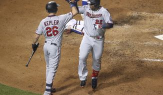 Minnesota Twins' Miguel Sano, right, celebrates with Max Kepler, left, after hitting a solo home run off Chicago Cubs starting pitcher Alec Mills during the seventh inning of a baseball game, Saturday, Sept. 19, 2020, in Chicago. (AP Photo/Kamil Krzaczynski)