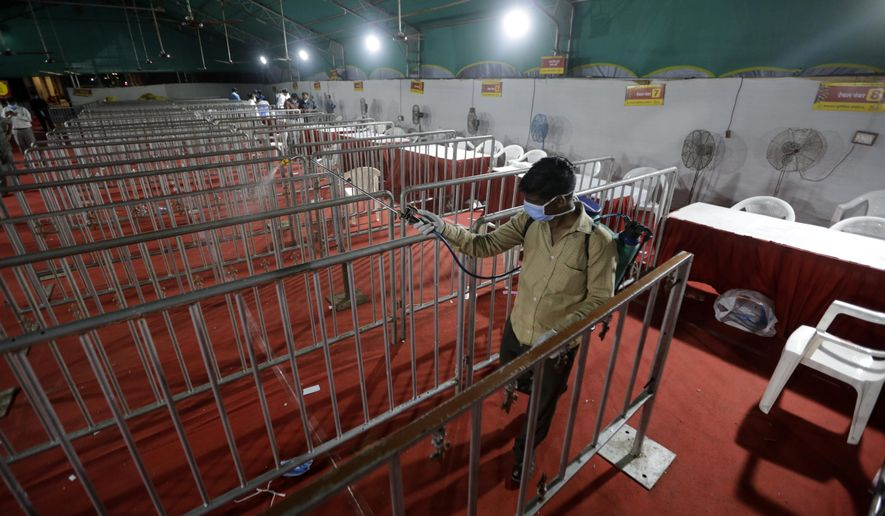 A health worker disinfects and area where tests for COVID-19 were performed, at a facility erected at a railway station to screen people coming from outside the city, in Ahmedabad, India, Friday, Sept. 18, 2020. India's coronavirus cases jumped by another 96,424 in the past 24 hours, showing little sign of leveling. India is expected to have the highest number of confirmed cases within weeks, surpassing the United States, where more than 6.67 million people have been infected. (AP Photo/Ajit Solanki)