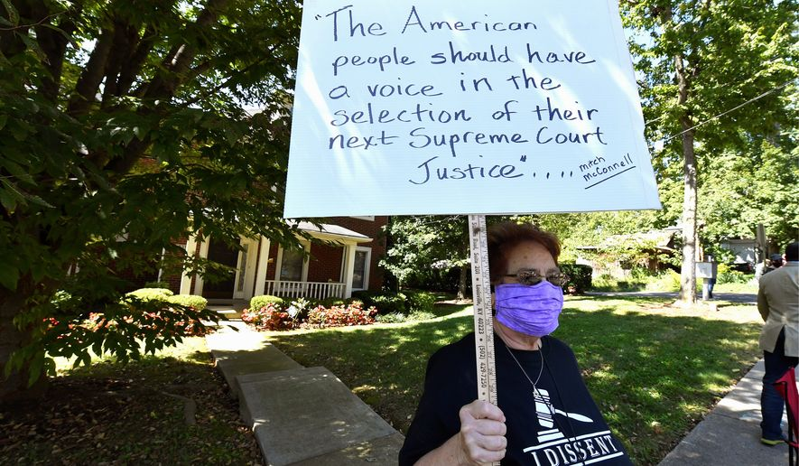A protester stands outside the house of Senate Majority Leader Mitch McConnell in Louisville, Kentucky, on Saturday. More protests are expected to follow. (Associated Press)