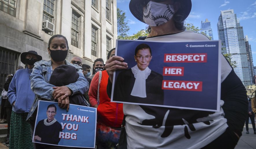 People hold signs of tribute during a public remembrance to honor the life and legacy of U.S. Supreme Court Justice and former Brooklynite Ruth Bader Ginsburg, outside Brooklyn's, Municipal Building, Sunday Sept. 20, 2020, in New York. Brooklyn Borough President Eric Adams is calling on Mayor Bill de Blasio to rename the Municipal Building in honor of Justice Ginsburg, a Brooklynite who passed away Friday at the age of 87. (AP Photo/Bebeto Matthews)