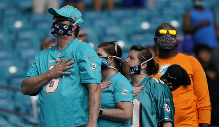 Fans stand for the National Anthem, during the first half of an NFL football game between the Miami Dolphins and the Buffalo Bills, Sunday, Sept. 20, 2020, in Miami Gardens, Fla. (AP Photo/Lynne Sladky)
