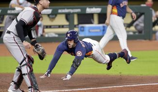 Houston Astros George Springer, right, dives for home plate on his inside the park home run as Arizona Diamondbacks catcher Carson Kelly, left, waits for the ball during the sixth inning of a baseball game Sunday, Sept. 20, 2020, in Houston. (AP Photo/Michael Wyke)