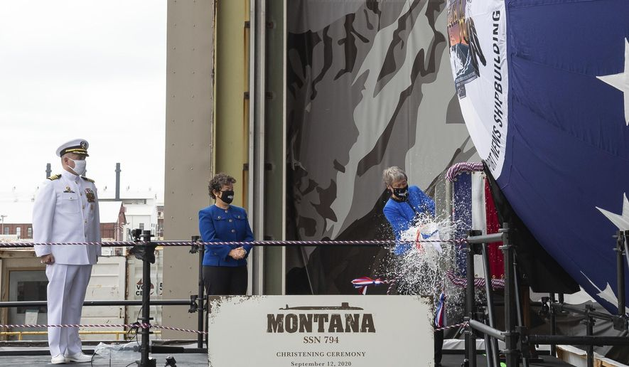 In this photo provided by  Huntington Ingalls Industries, the ship's sponsor, former Secretary of the Interior Sally Jewell, right, christens the Virginia-class submarine USS Montana, also known as SSN 794, as the ship's commanding officer Capt. Michael Delaney, left, and Newport News Shipbuilding President Jennifer Boykin, look on during its christening ceremony on Saturday, Sept. 12, 2020 in Newport News, Va. (Matt Hildreth/Huntington Ingalls Industries via AP)
