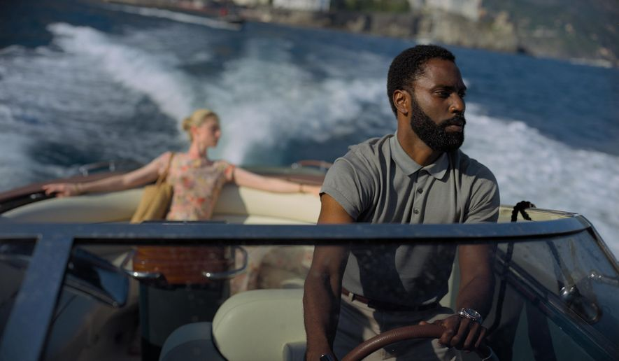 """This image released by Warner Bros. Entertainment shows Elizabeth Debicki, left, and John David Washington in a scene from """"Tenet.""""  As """"Tenet"""" enters its third week in North American cinemas with barely any new blockbusters on the horizon, U.S. exhibitors are put in a tricky spot. (Melinda Sue Gordon/Warner Bros. Entertainment via AP)"""