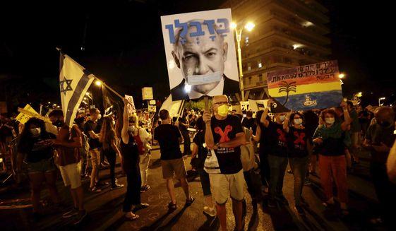 Israeli protesters hold signs and chant slogans during a demonstration against Israeli Prime Minister Benjamin Netanyahu near the Prime Minister's residence in Jerusalem, Sunday, Sept. 20, 2020. (AP Photo/Sebastian Scheiner)