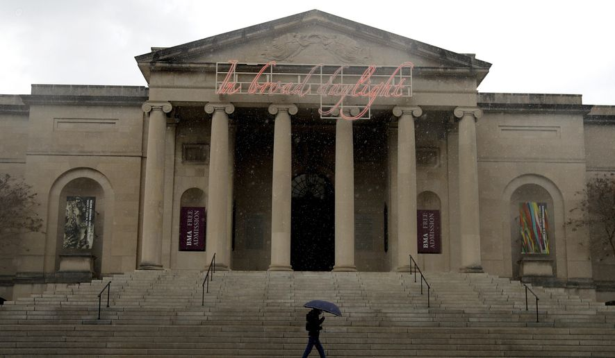FILE - In this April 21, 2020 file photo, a man covers himself from rain with an umbrella as he walks in front of the Baltimore Museum of Art in Baltimore.  With every face mask, bottle of hand sanitizer and pair of disposable gloves it acquires, the Baltimore Museum of Art is moving one more socially distanced step closer to reopening fully to the public, six months after locking its doors as the coronavirus pandemic descended on Maryland. The state's largest museum began welcoming visitors Sept. 16, though the capacity was limited and galleries will reopen in phases.  (AP Photo/Julio Cortez, File)