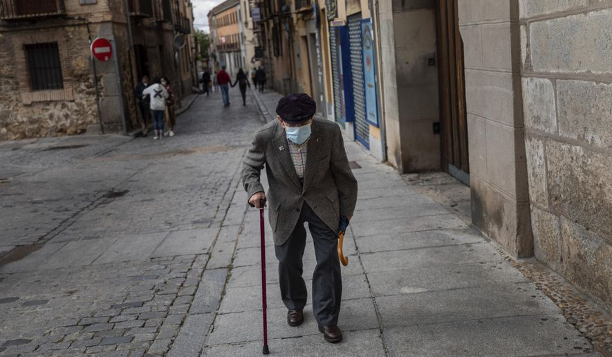 An elderly man wearing a face mask to prevent the spread of coronavirus walks in downtown Segovia, central Spain, Saturday, Sept. 19, 2020. Spain has been the hardest hit European country in the second wave of the pandemic. (AP Photo/Bernat Armangue)