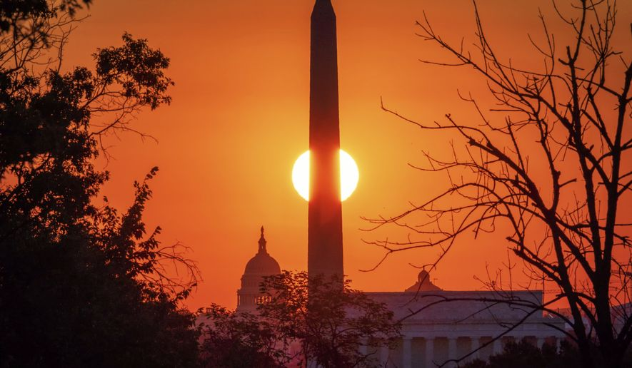 The sun rises behind the Washington Monument on the last day of summer in Washington, Monday, Sept. 21, 2020. The Autumn equinox in the northern hemisphere is Tuesday, Sept. 22 which ushers in the first day of fall. (AP Photo/J. David Ake)