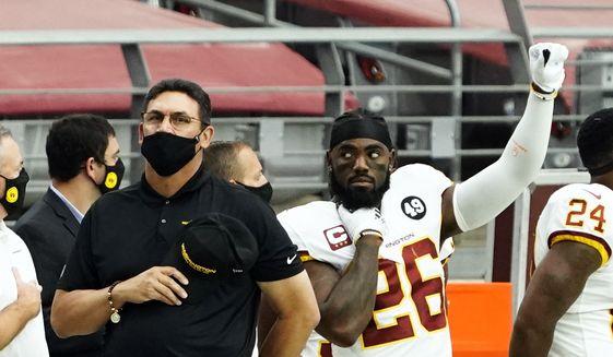 Washington Football Team head coach Ron Rivera and Landon Collins (26) before an NFL football game against the Arizona Cardinals, Sunday, Sept. 20, 2020, in Glendale, Ariz. (AP Photo/Rick Scuteri)  **FILE**