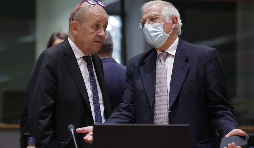 French Foreign Minister Jean-Yves Le Drian, left, speaks with European Union foreign policy chief Josep Borrell during a meeting of EU foreign affairs ministers at the European Council building in Brussels, Monday, Sept. 21, 2020. (Olivier Hoslet, Pool via AP)