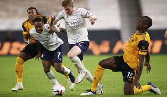 Manchester City's Kevin De Bruyne centre, takes the ball say from Wolverhampton Wanderers' Willy Boly, right, during the English Premier League soccer match between Wolverhampton Wanderers and Manchester City at Molineux Stadium in Wolverhampton, England, Monday, Sept. 21, 2020. (Marc Atkins/Pool via AP)