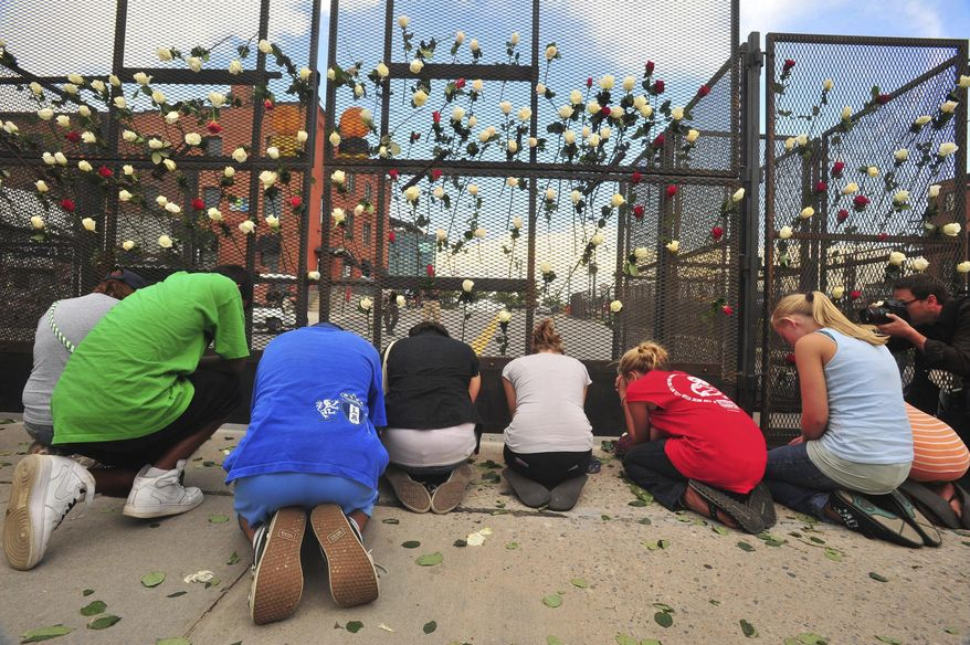 Pro-life activiststs pray under a fence of roses in Denver. (AP Photo/Bill Ross, File)