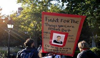 FILE - In this Saturday, Sept. 19, 2020, file photo, a sign featuring a likeness of Justice Ruth Bader Ginsburg is carried in Washington Square Park in New York, a day after the death of the Supreme Court justice. The political battle is being quickly joined over replacing Ginsburg on the Supreme Court. (AP Photo/Craig Ruttle, File)