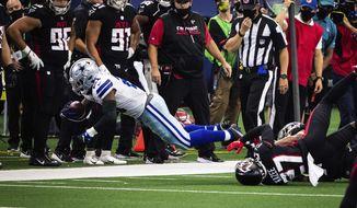Dallas Cowboys running back Ezekiel Elliott gets tripped up by an Atlanta Falcons defender Sunday, Sept. 20, 2020, in Arlington, Texas. (Yffy Yossifor/Star-Telegram via AP)