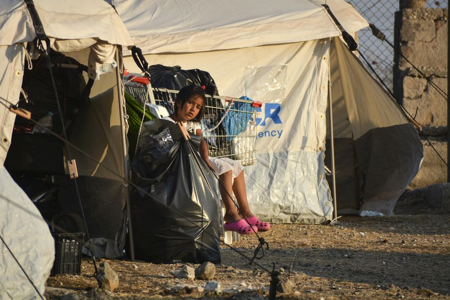A child sits inside the new temporary refugee camp in Kara Tepe, on the northeastern island of Lesbos, Greece, Saturday, Sept. 19, 2020. Police on the Greek island of Lesbos on Friday resumed relocating migrants rendered homeless when fires ravaged the country's largest refugee camp amid a local COVID-19 outbreak. (AP Photo/Panagiotis Balaskas)