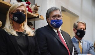 U.S. Attorney General William Barr, center, Georgia Gov. Brian Kemp, right and a Georgia Center for Child Advocacy staff member listen during a tour on Monday, Sept. 21, 2020, in Atlanta. (AP Photo/Brynn Anderson)