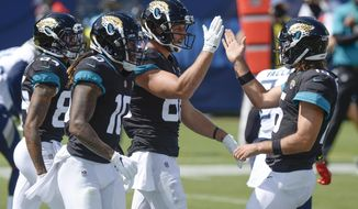 Jacksonville Jaguars tight end Tyler Eifert (88) is congratulated by quarterback Gardner Minshew, right, after teaming up for a 19-yard touchdown pass against the Tennessee Titans in the first half of an NFL football game Sunday, Sept. 20, 2020, in Nashville, Tenn. (AP Photo/Mark Zaleski)