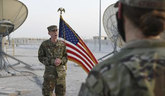 In this photo released by the U.S. Air Force, Col. Todd Benson, the U.S. Air Force Central Command director of space forces, addresses members of the 379th Operations Support Squadron before they are sworn in as members of the Space Force at Al-Udeid Air Base, Qatar, Tuesday, Sept. 1, 2020. Space Force, the first new U.S. military service since the creation of the Air Force in 1947, now has some 20 members stationed at the Qatari base in its first foreign deployment. (Staff Sgt. Kayla White/U.S. Air Force via AP) **FILE**