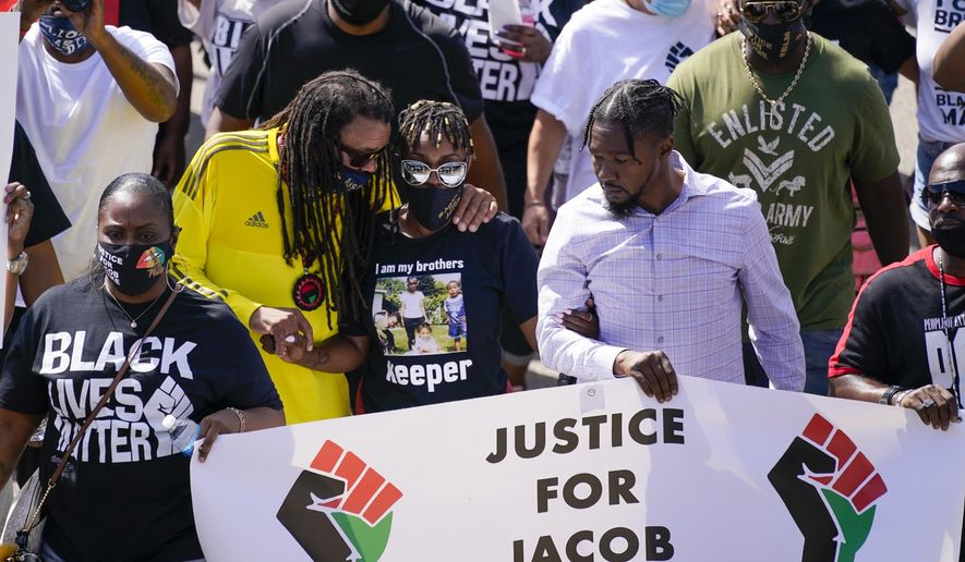 FILE - In this Aug. 29, 2020, file photo, Jacob Blake's sister Letetra Widman, center, and uncle Justin Blake, left, march at a rally for Jacob Blake in Kenosha, Wis. Wisconsin's attorney general planned to provide an update Monday, Sept. 21, 2020 on the investigation into the police shooting of Blake, a Black man who was shot in the back by a white police officer last month, sparking days of protests. (AP Photo/Morry Gash, File)