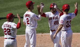 Los Angeles Angels' Jared Walsh (25) celebrates with David Fletcher, left, Andrelton Simmons and Max Stassi, right, who all scored on Walsh's grand slam during the fourth inning of a baseball game against the Texas Rangers, Monday, Sept. 21, 2020, in Anaheim, Calif. (AP Photo/Ashley Landis)
