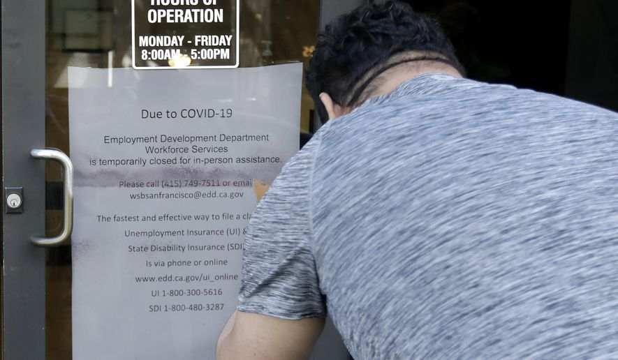 In this March 26, 2020, file photo a man takes a photo of a sign advising that the Employment Development Department is closed due to coronavirus concerns, in San Francisco. A review of California's unemployment agency has found its productivity level declined despite hiring hundreds of new workers. The Employment Development Department has been overwhelmed by millions of claims for unemployment benefits during the coronavirus pandemic. (AP Photo/Jeff Chiu, File)