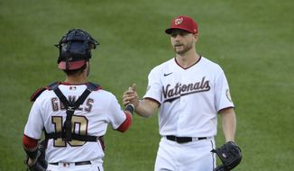 Washington Nationals starting pitcher Austin Voth, right, celebrates his complete-game win with catcher Yan Gomes after the first baseball game of a doubleheader against the Philadelphia Phillies, Tuesday, Sept. 22, 2020, in Washington.  (AP Photo/Nick Wass)