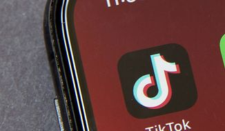In this Friday, Aug. 7, 2020, photo, the icons for the smartphone app TikTok on a smartphone screen in Beijing. (AP Photo/Mark Schiefelbein) **FILE**